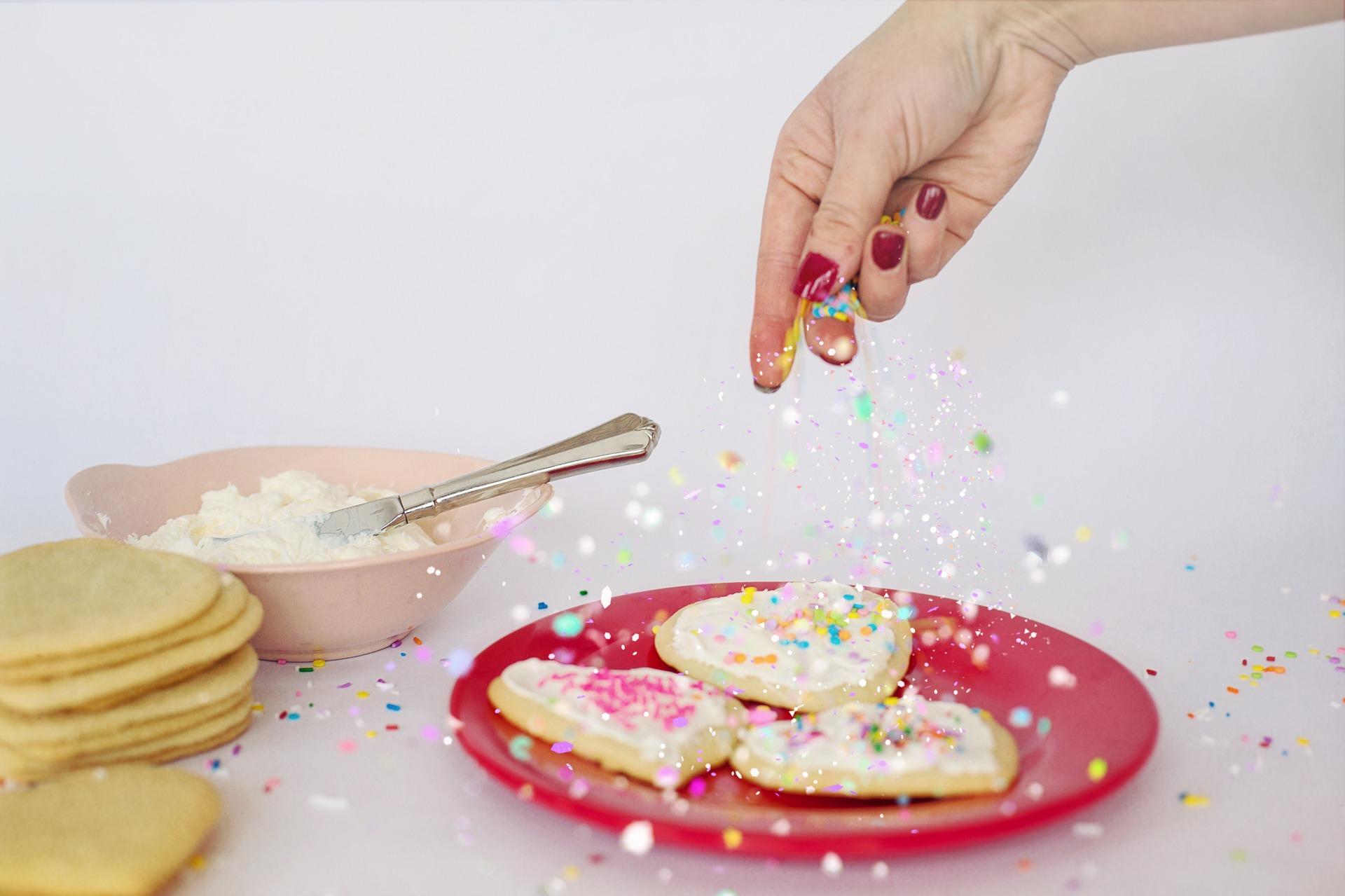Sugar Cookie Decorating, hand dropping sprinkles onto cookies.
