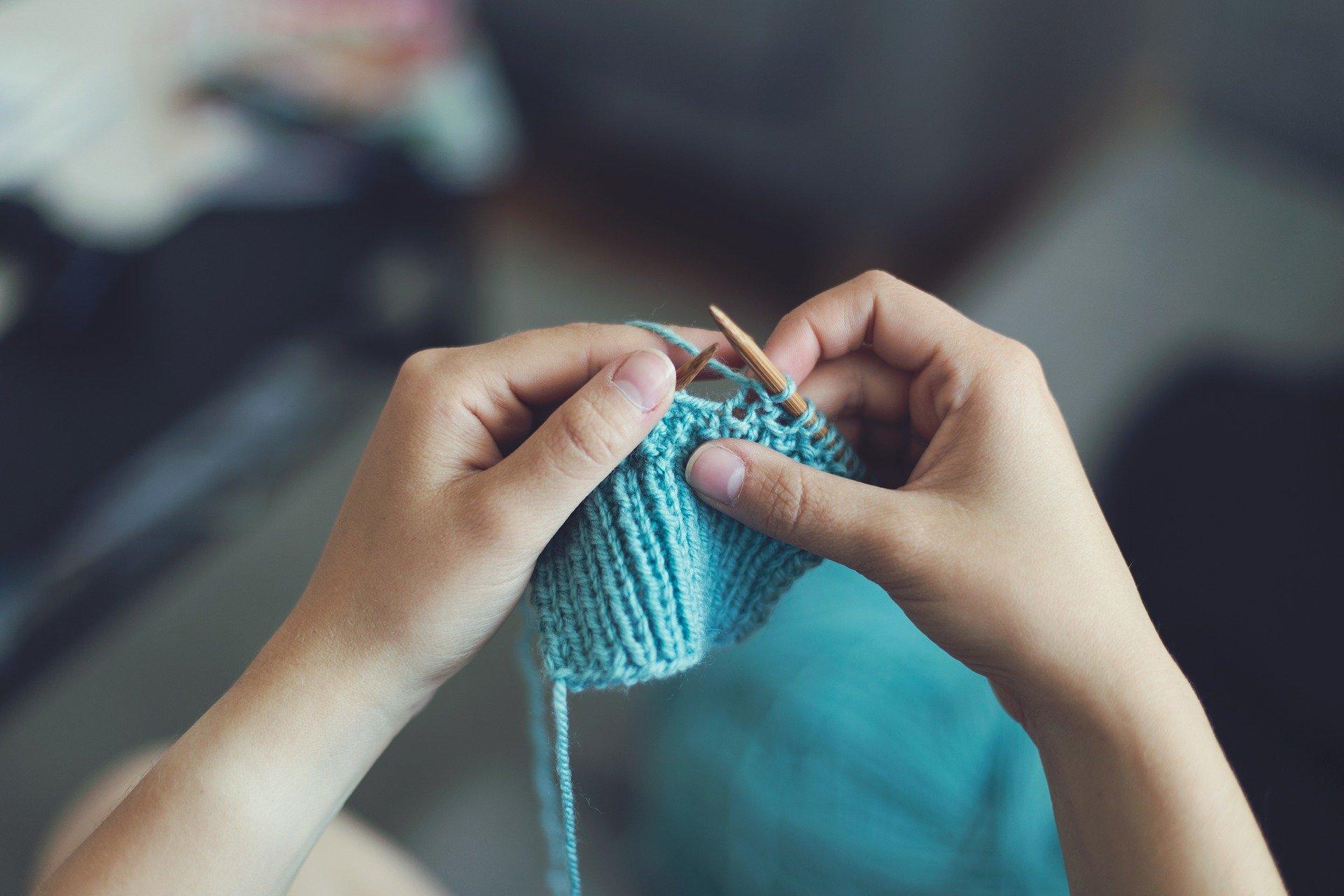 Person holding blue yarn, knitting.