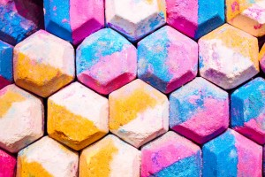 Colorful hexagonal chalk pieces colored gold, peach, blue, and pink.