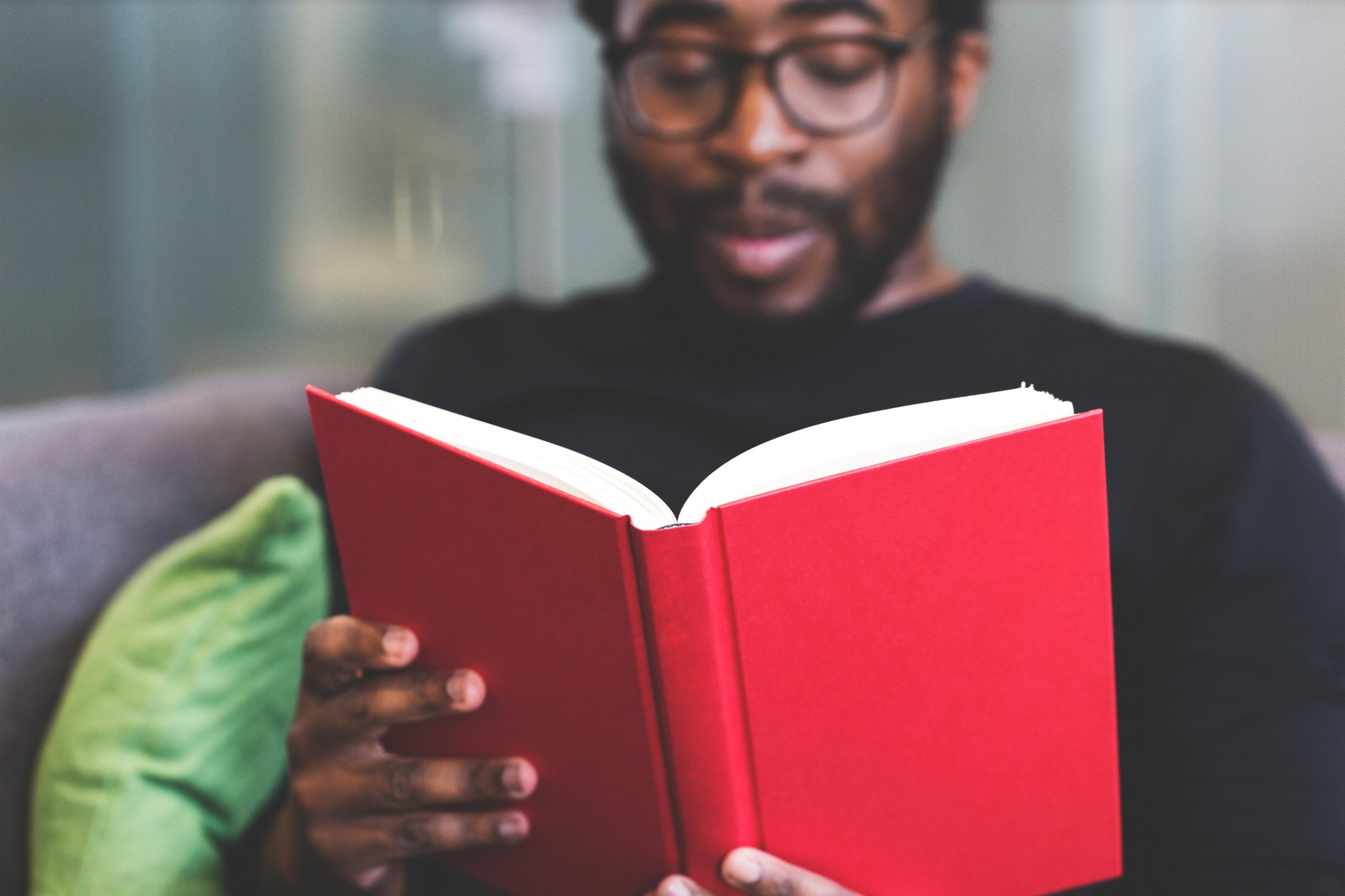 Man with Glasses reading a red hardcover book.