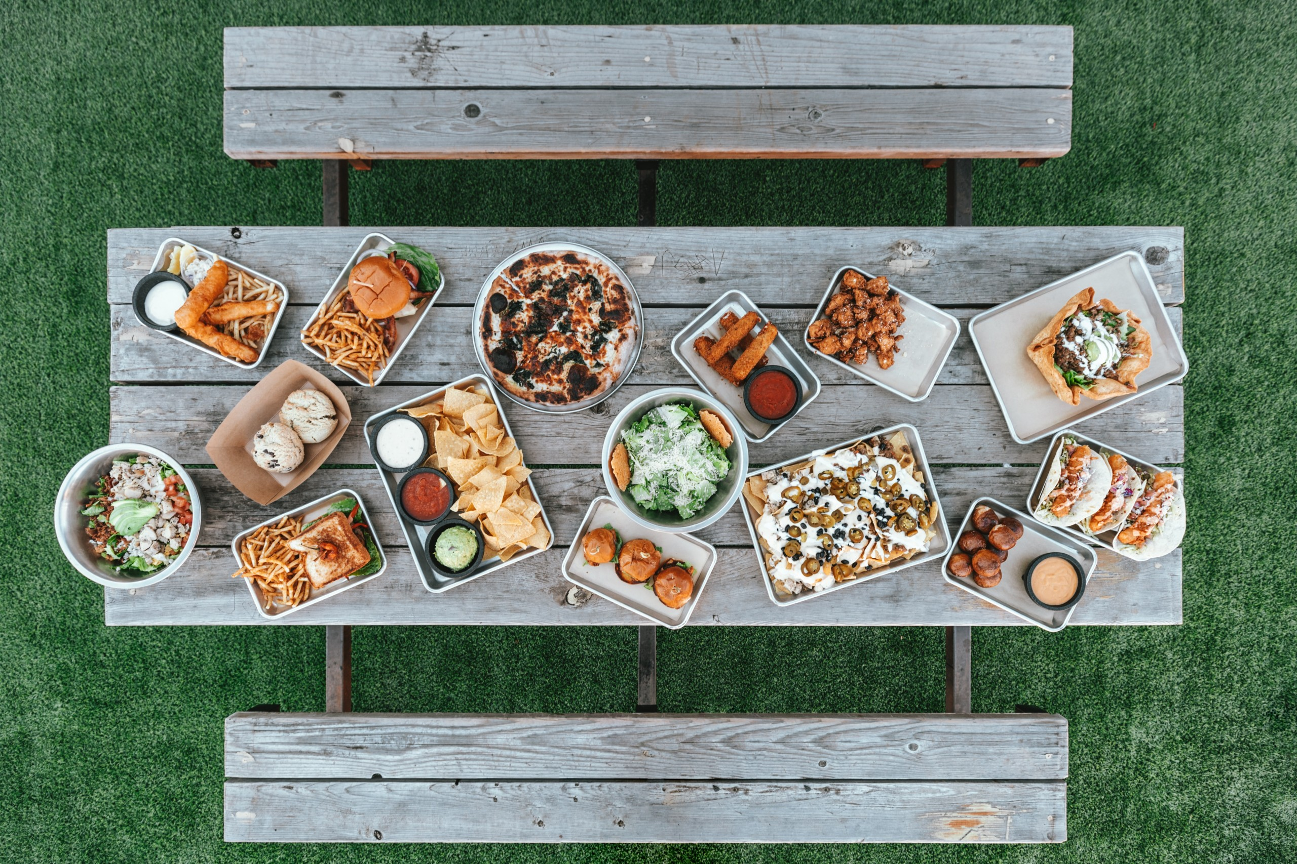 Picnic table outside filled with plates of food.
