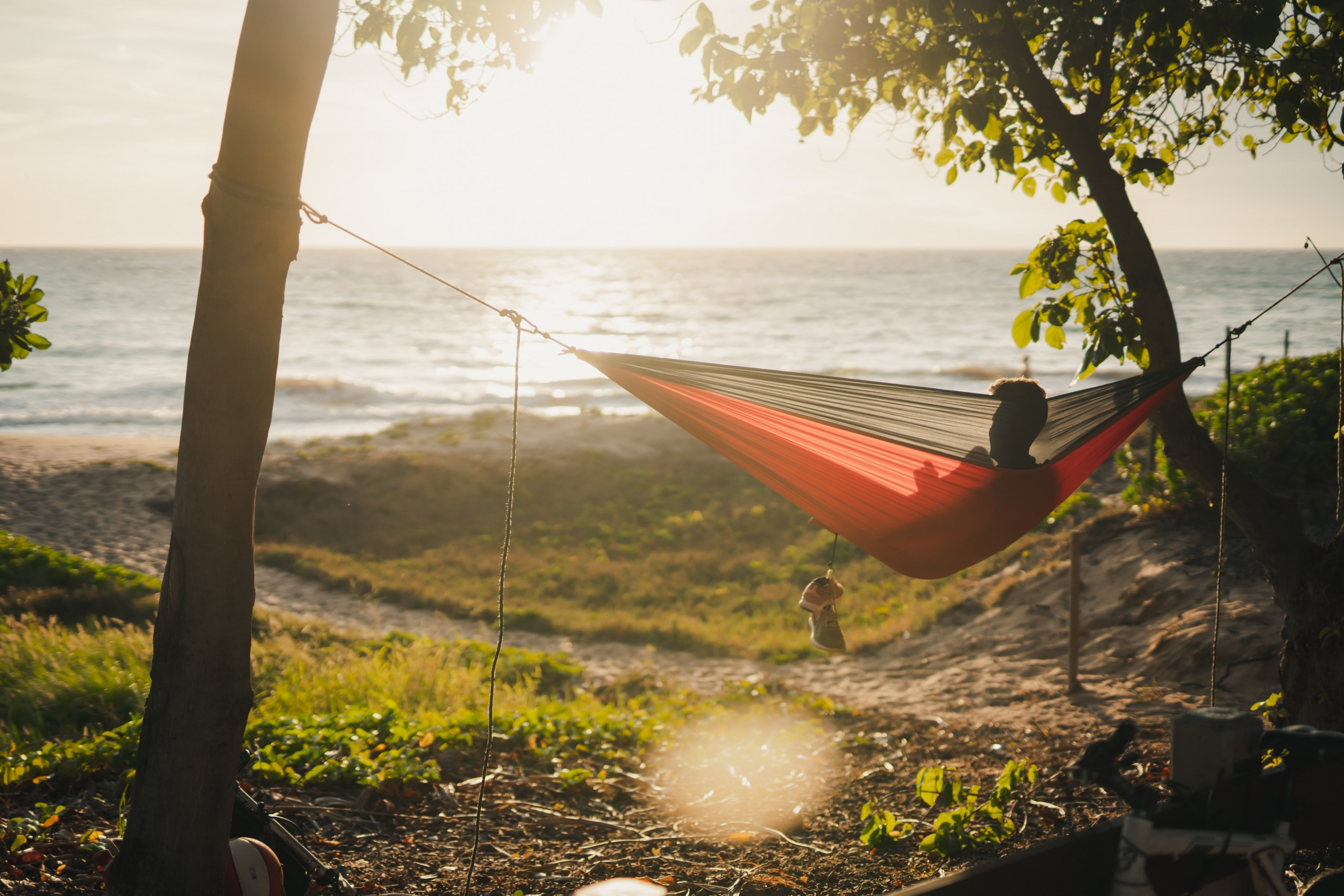 Person in Hammock facing Sunset over Water.