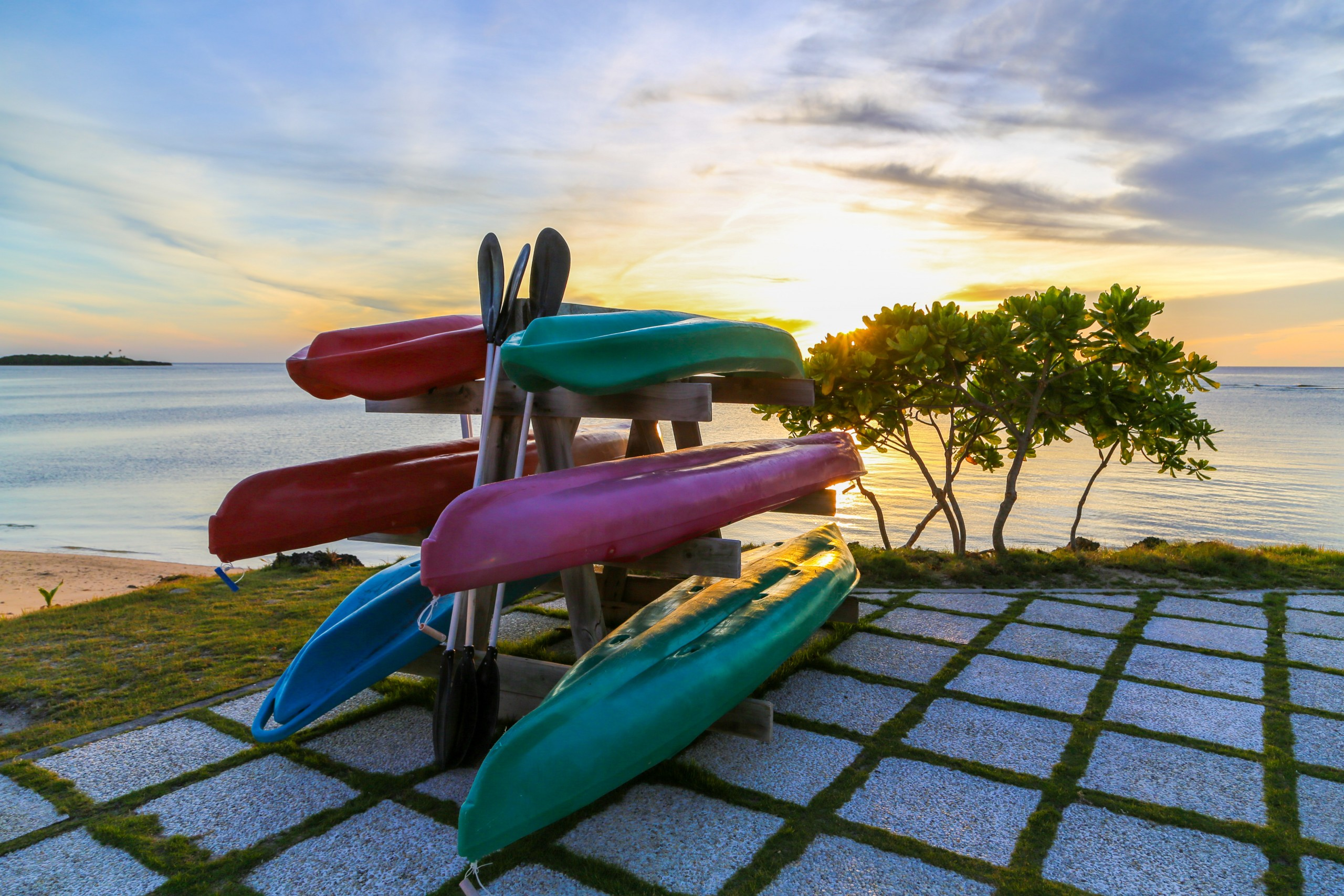 Colorful kayaks on rack with sunset in background.