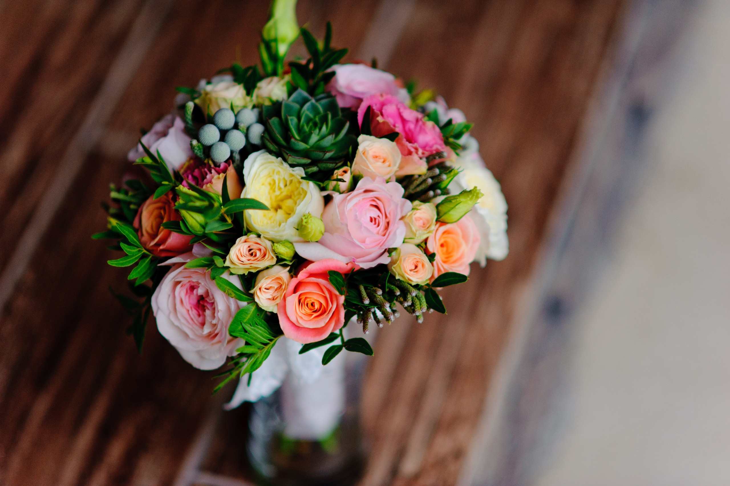 Flower bouquet in vase on table with pink, yellow, and orange roses.