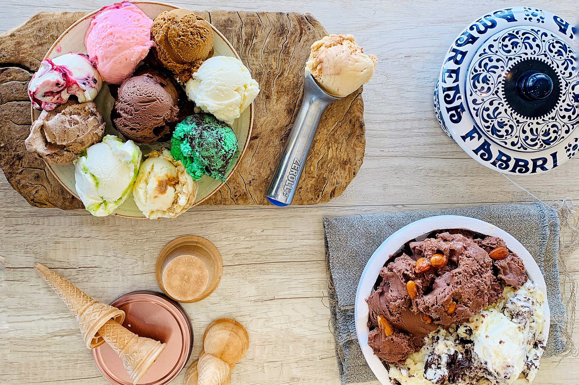 Ice cream scoops, scooper, cones, and sundae bowl on table.