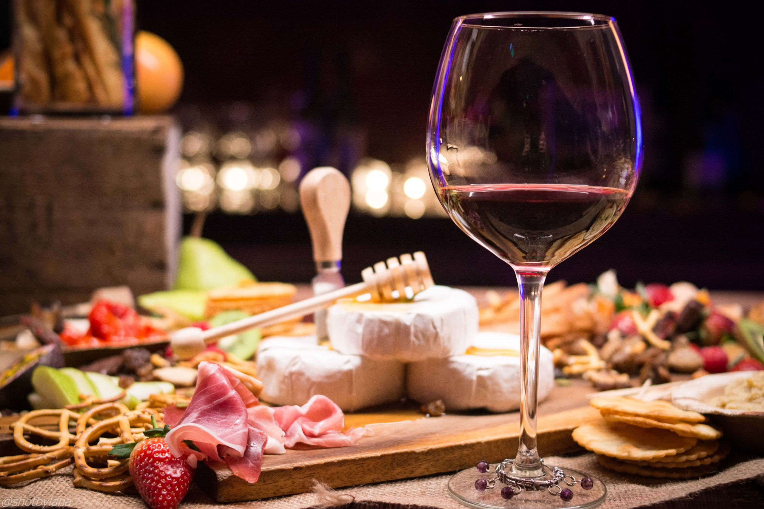 Wine glass on counter with cheese and meat spread.