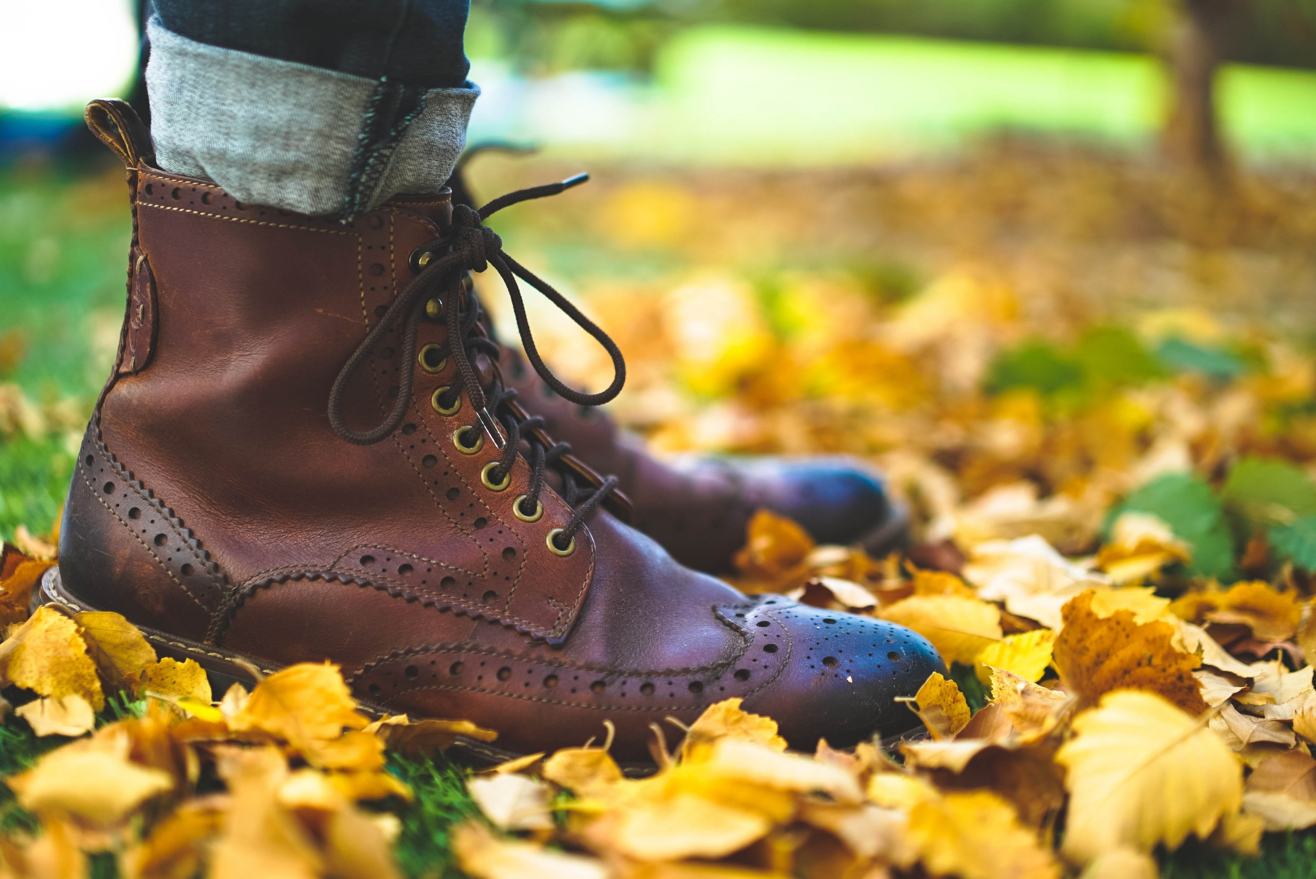 Brown fashion boots with high-top laces in yellow fall leaves.