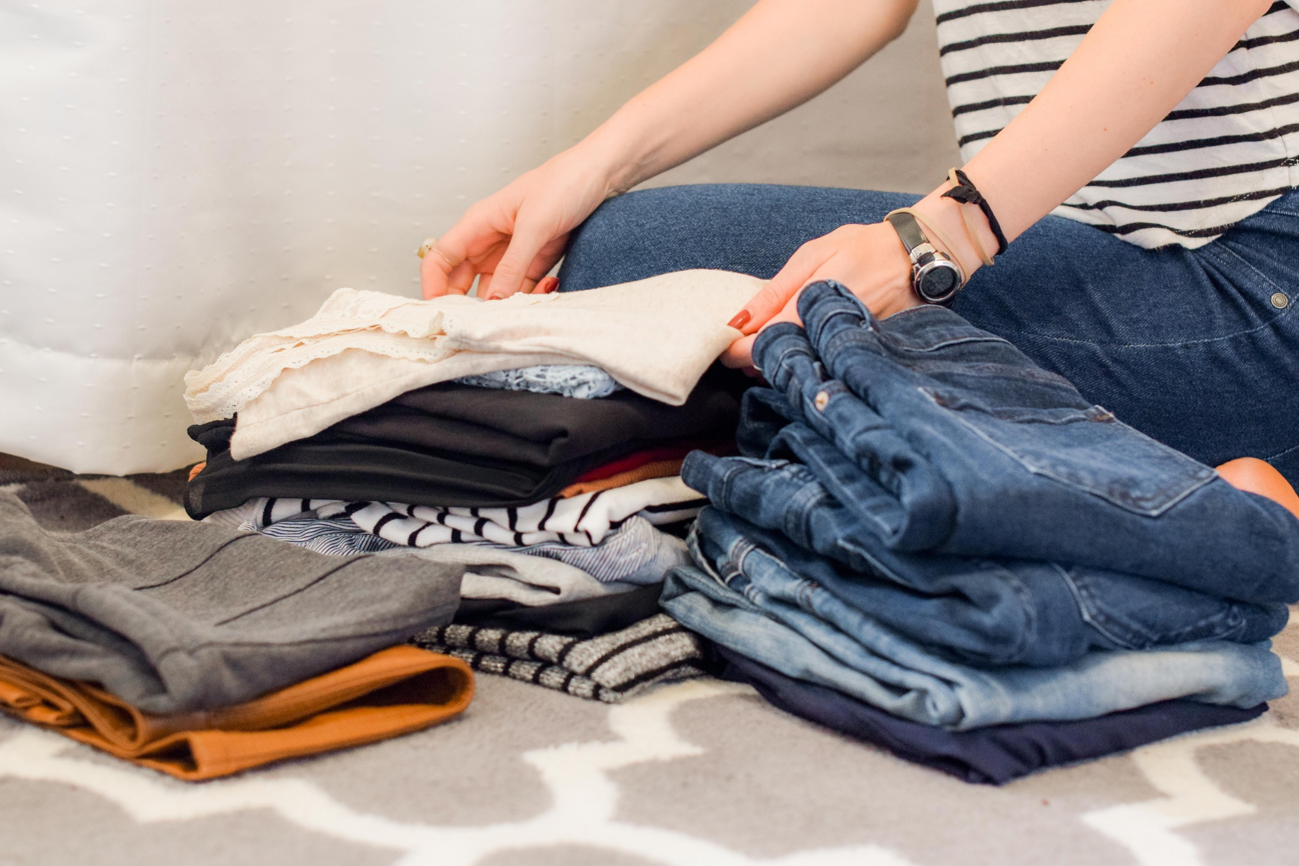 Person folding and sorting clothes into piles. Shirts and Jeans.