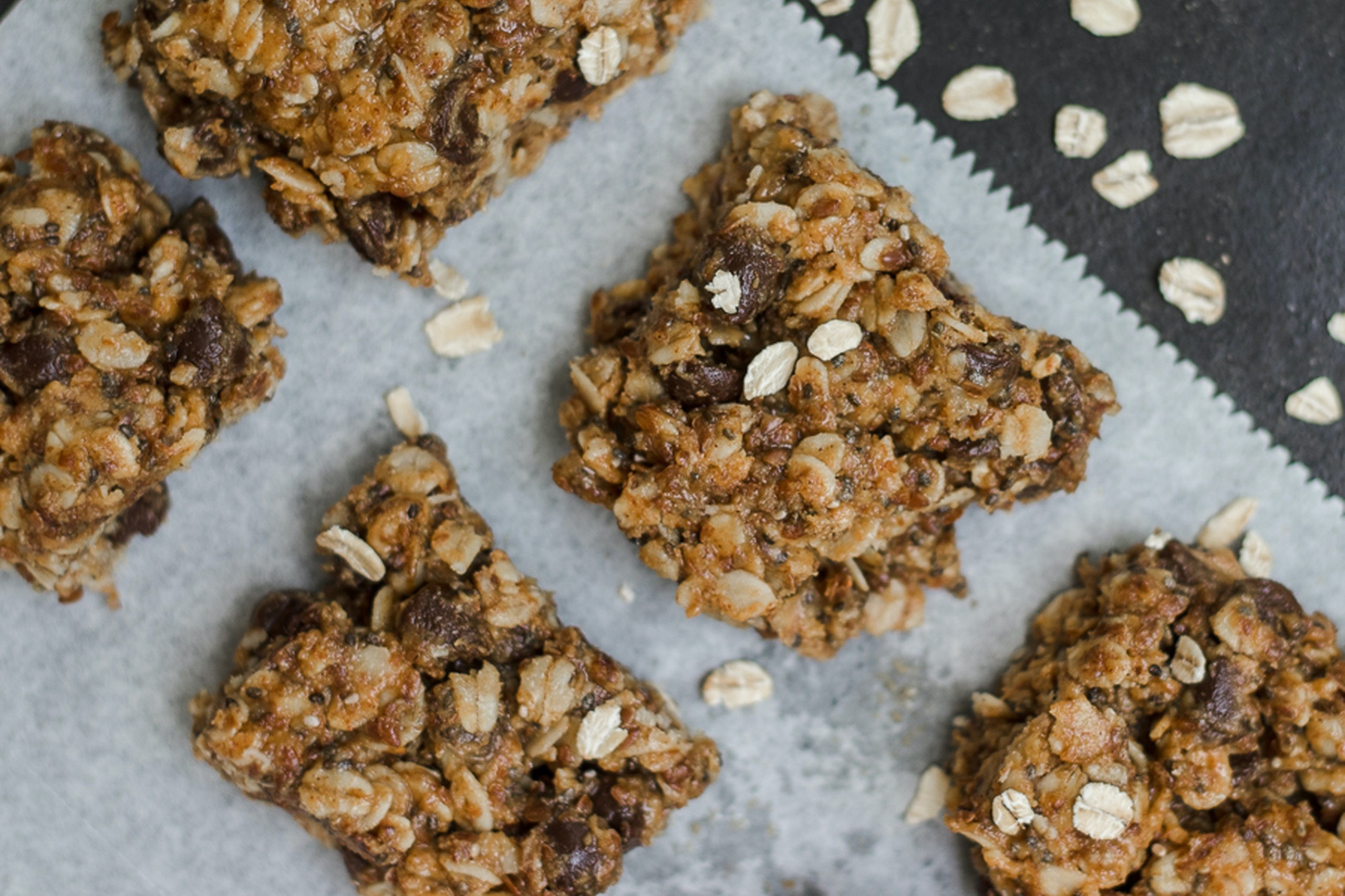 Granola bars with chocolate chips on wax paper.