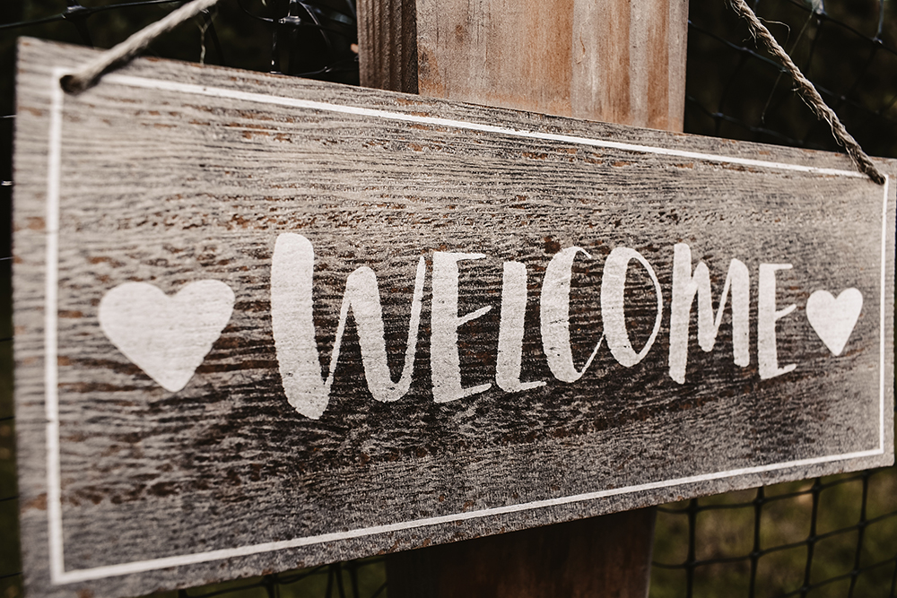"Hand-painted wooden sign with hearts that says ""Welcome."""