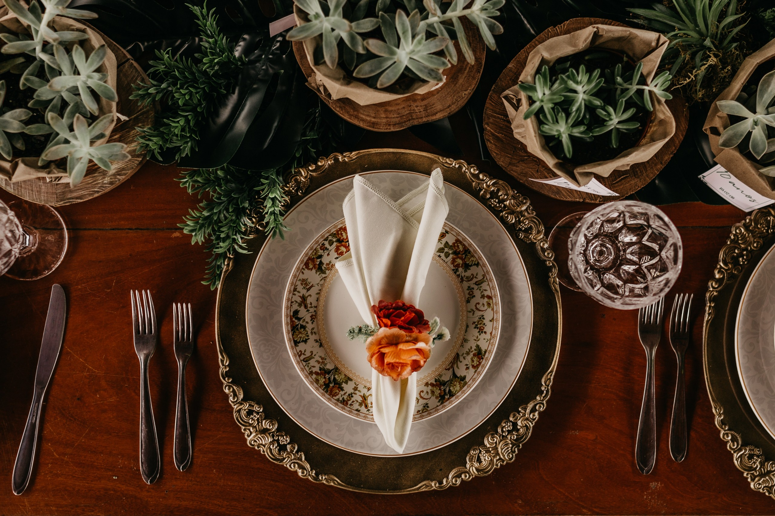 Table setting with ornate gold charger, and floral patterned plates. Silverware, and succlents surround the plate on wooden table.