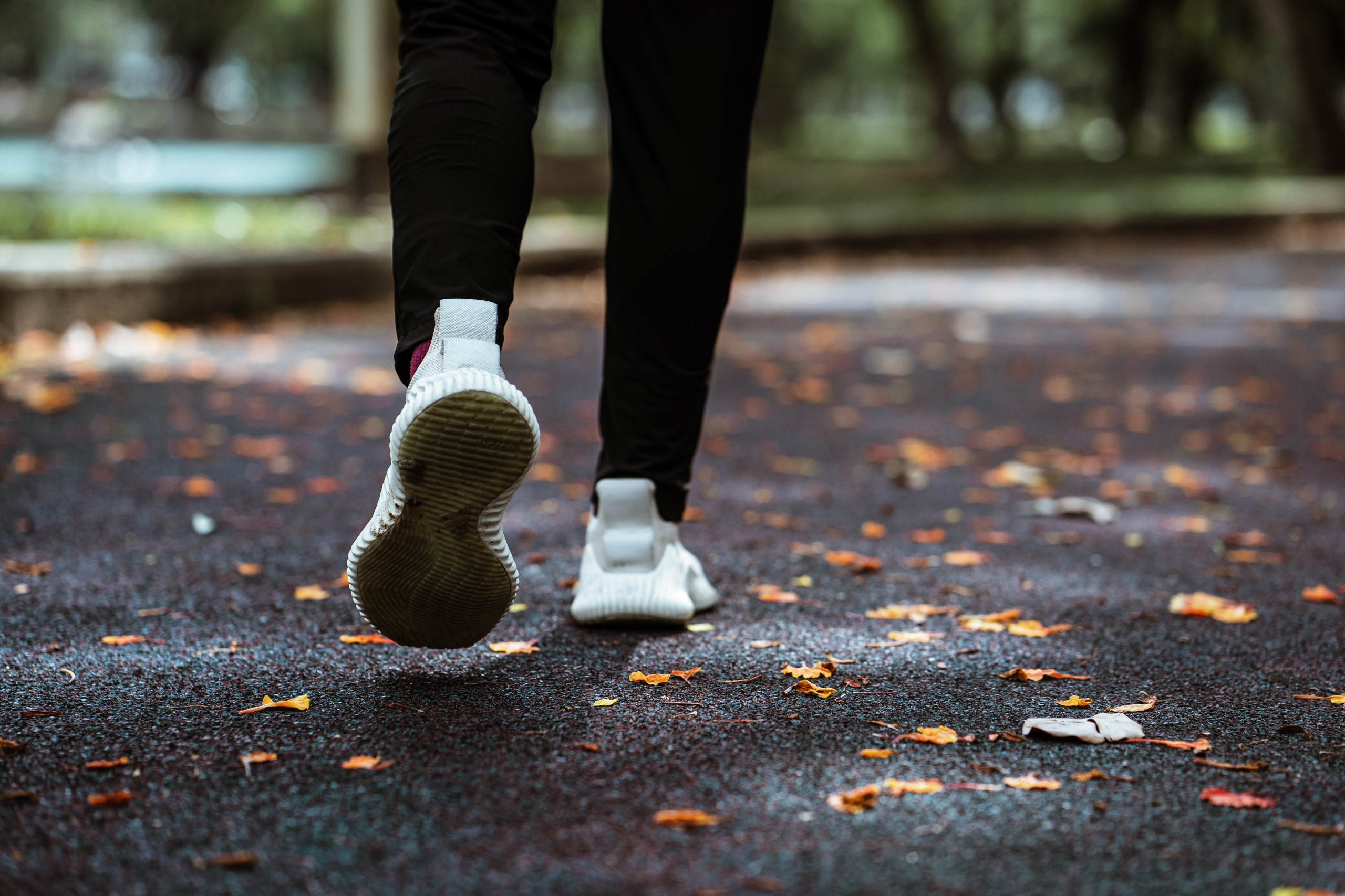 Person running outside on pavement. Fall leaves on ground. View of black pants and white tennis shoes.