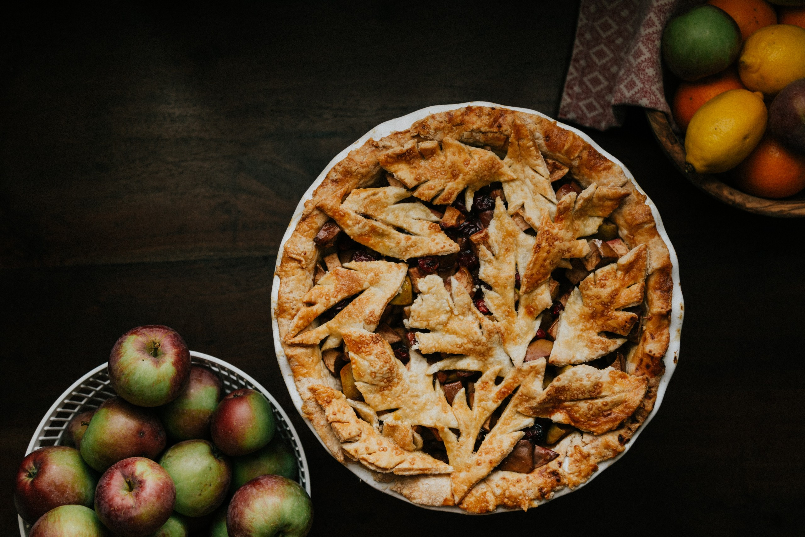 Apple Pie on Table with bowls of fruit next to it.