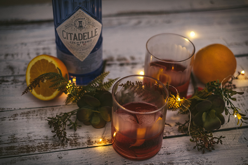 Festive holiday drinks on table with grennery and oranges