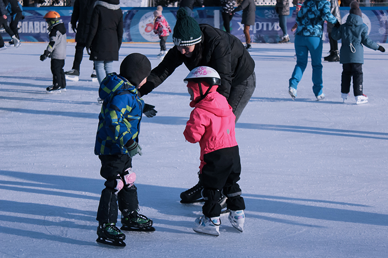 Parent and children ice skating outdoors.