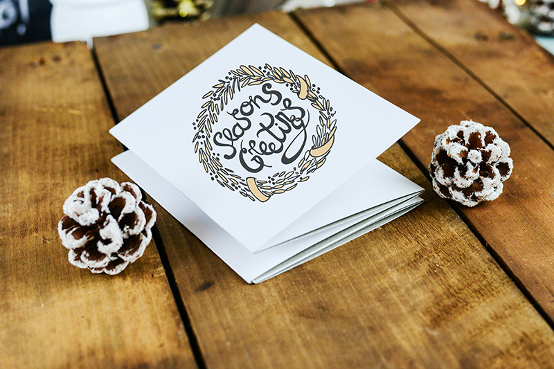 """White card next to pinecones on wood table: """"Season's Greetings"""""""