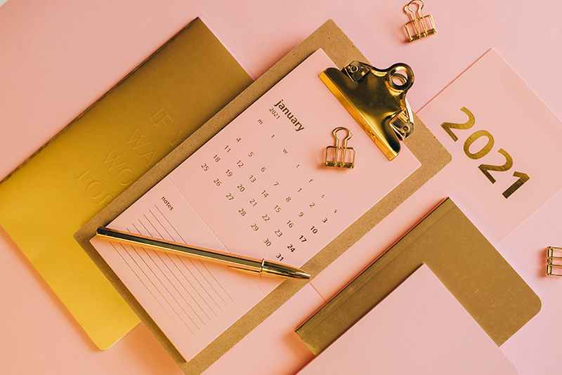Pink January calendar on clipboard. 2021 in gold letters with notebooks.